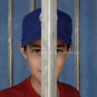 22/8/2010. Bethlehem (Palestinian Territories). Palestinian child at the checkpoint. When open, waiting time at checkpoints varies between 10-15 minutes to 2 hours, depending on the time of the day, on the number of people waiting, on the number of lanes funcitioning and most important on the mood of the soldiers.