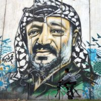 A boy passing-by a graffiti of the historical palestinian leader Yasser Arafat painted on the separation wall built by Israel around the Occupied Territories