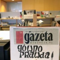 "Gazeta Wyborzca is the most important newspaper in Poland, it is strongly critic with the right-wing and ultra-catholic governament appointed by president Andrzej Duda. in the foreground a placard against the newspaper from pro-governament demonstrators which says: ""your truth is shit"""