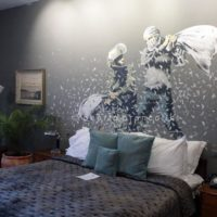 "The Walled Off Hotel is a recentely opened hotel owened by Banksy, the famous graffiti artist. The hotel is located next to the separation wall and decorated with graffiti made by Banksy himself, in this photo ""The Pillow Fight"""